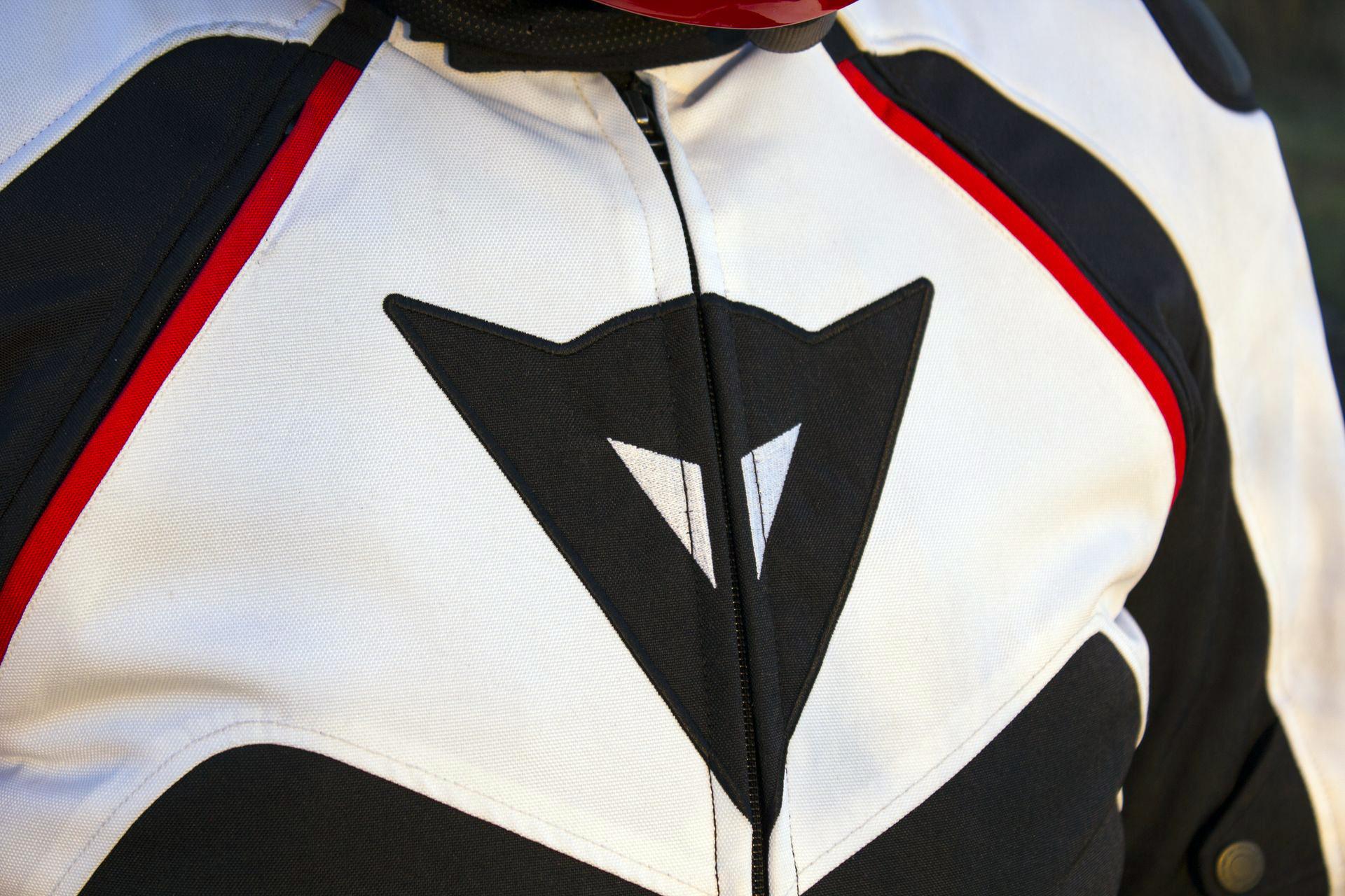 El gran logotipo, típico de las chaquetas deportivas Dainese, está presente en el torso. Observad las dos cremalleras con su ribete rojo.