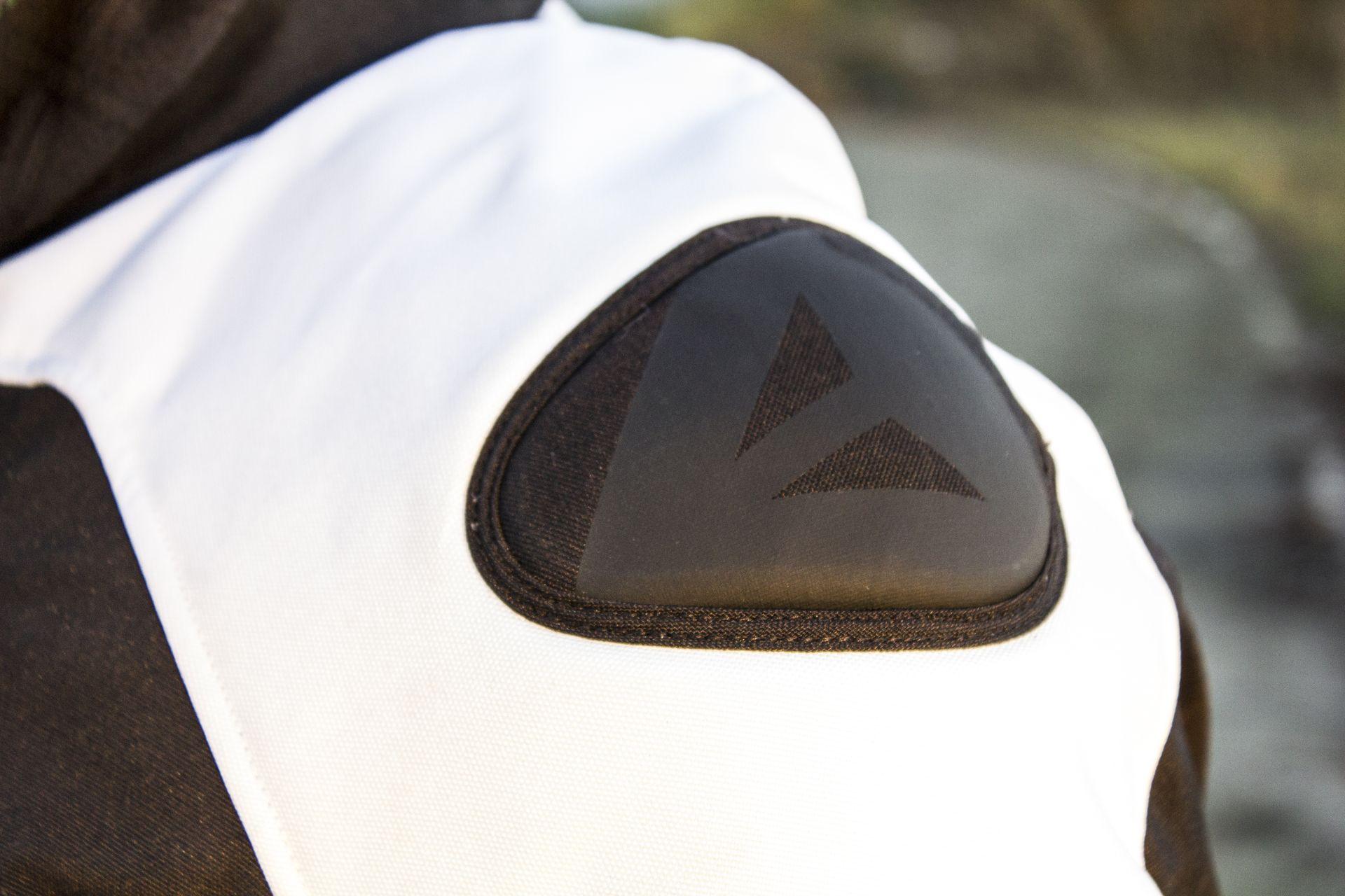 Refuerzo de plástico cubierto con tela y decorado con el logotipo de Dainese: algo que recuerda a los modelos racing de la marca
