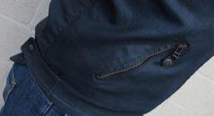 Zoom de uno de los bolsillos laterales y del ajuste de la cintura mediante broches de presión